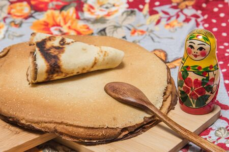 rite: Buttercakes traditional for Russian pancake week and Russian nesting doll on wooden cutting plate