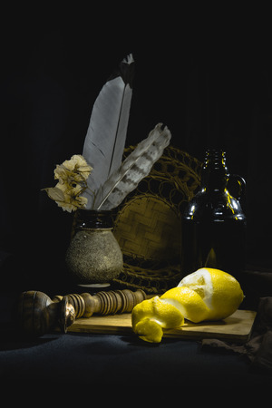 Low-key Studio Shot of a lemon near the smoking pipe and vase with feathers isolated over black background