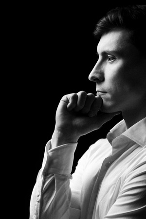 Low key portrait of a man in white shirt in black and white.