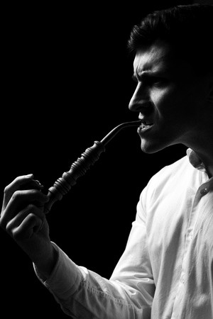 Low key portrait of a man with pipe in white shirt in black and white. Stock Photo