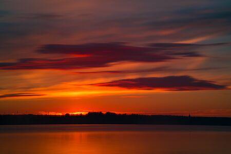 Orange or red sunset at coast of the lake