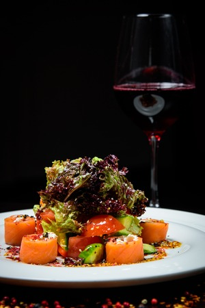 Leaf vegetable salad with smoked salmon.,Red fish healthy salad with mixed lettuce leaves, olives and tomatoes on a white dish near the glass of wine. Black background Stock Photo