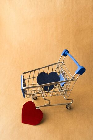 blue and red hearts in a shopping cart on a craft background