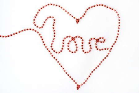 The word LOVE - declaration of written with red beads isolated on white background Stock Photo