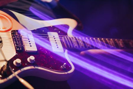 closeup rockstar on stage playing on electro guitar. Male guitarist Stock Photo