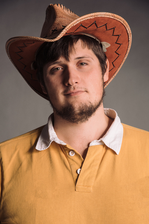 A big man in a cowboy hat and a yellow shirt. Young man. The studio shot in the gray wall.