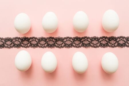 white eggs on pink pastel background. minimal concept. top view