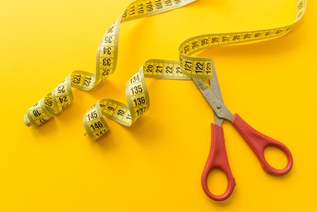 Red scissors with tailors meter on orange or yellow background. minimal concept. top view. diet