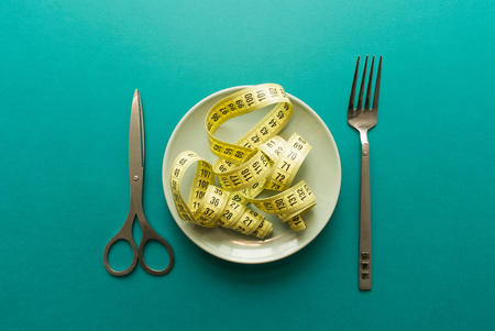 Tailors meter on plate like chinese noodles on green background. minimal concept. top view. diet,
