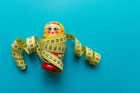 Nesting doll matrioshka with tailors meter on blue background. minimal concept. top view. Stock Photo