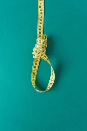 Tailors meter like gallows or running knot on green background. minimal concept. top view. diet Stock Photo