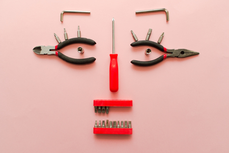 Conceptual set of tools on pink background. It looks like a woman face. Working handmade instruments.