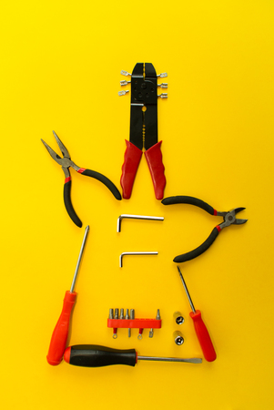 Conceptual set of tools on yellow background. It lookTop view. Stock Photo