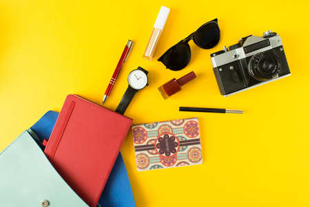 Flat lay of cute woman bag open out with passport, photo, accessories on colorful background with copy space Stock Photo