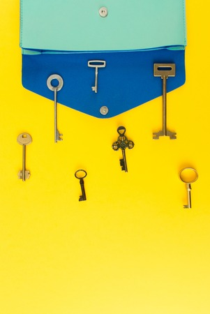 Flat lay of cute woman bag open out with a lot of old keys on colorful background with copy space.