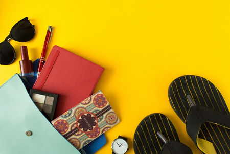 Flat lay of cute woman bag open out with passport, cosmetic, sunglasses, notebook, accessories and flip flops on colorful background with copy space. All you need to comfort travel. Stock Photo
