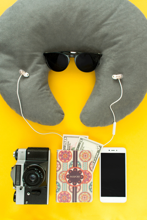 Portrait of tipical tourist: all you need in journey, voyage or travel. Passport, sunglasses, neck pillow, headphones, money, camera and smartphone. Stock Photo