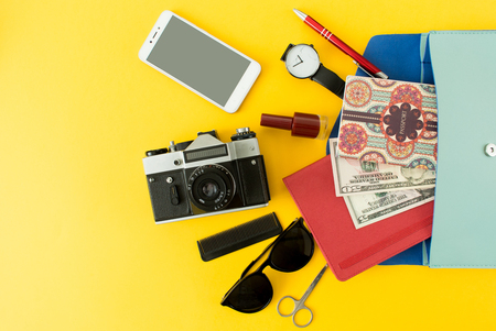 Flat lay of cute woman bag open out with passport, cosmetic, sunglasses, notebook, smartphone and camera on colorful background with copy space, top view. All you need to comfort travel. Stock Photo