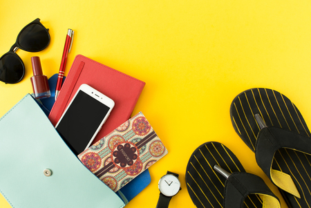 Flat lay of cute woman bag open out with passport, cosmetic, sunglasses, notebook, accessories, smartphone and flip flops on colorful background with copy space, top view.