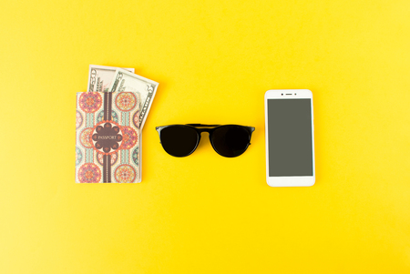 Portrait of objects: all you need in journey, voyage or travel. Passport, camera, sunglasses and smartphone.