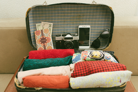 Open vintage leather travel valises or old suitcase with clothes, passport, camera and sunglasses for comfort voyage.