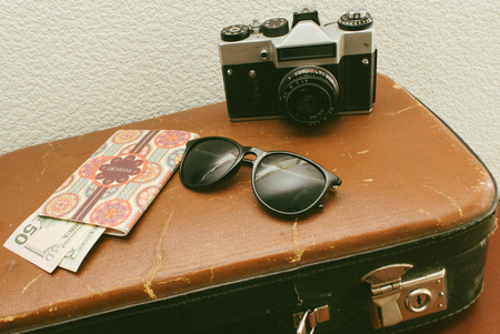 Vintage leather travel valises or old suitcase with passport, money, camera and sunglasses. Stock Photo