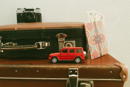 Part of vintage leather travel valises or old suitcase with passport, money, camera and toy car. Stock Photo