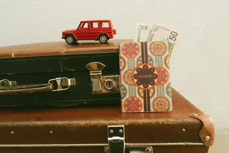 Part of vintage leather travel valises or old suitcase with passport, money, camera and toy car. Close up