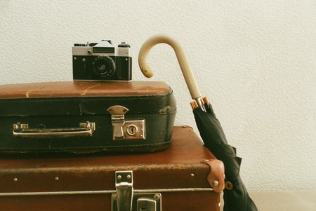 Part of vintage leather travel valises or old suitcase with camera and black umbrella. Stock Photo