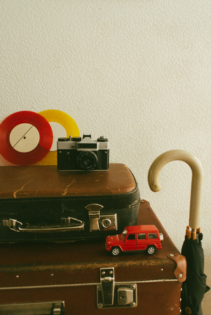 Part of leather travel valises or old suitcase with camera, toy car, vintage vinyl records and black walking stick. Stock Photo