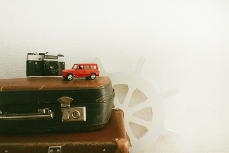 Part of leather travel valises or old suitcase with red toy car and vintage white steering wheel . Stock Photo