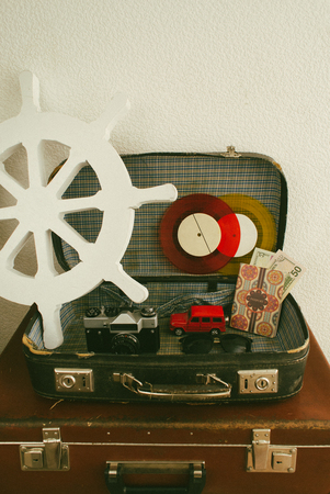 Part of leather travel valises or old suitcase with camera, toy car, vintage vinyl record and black walking stick.