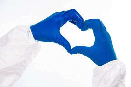 Doctor's or nurses hands in navy gloves making heart shape isolated on white background
