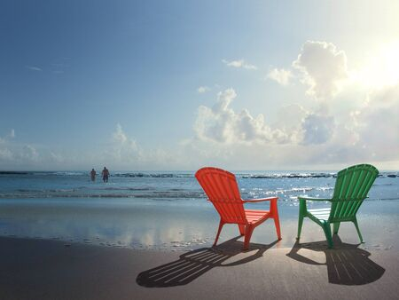 chairs: Two colorful Adirondack chairs at the beach and a couple in a distance Stock Photo