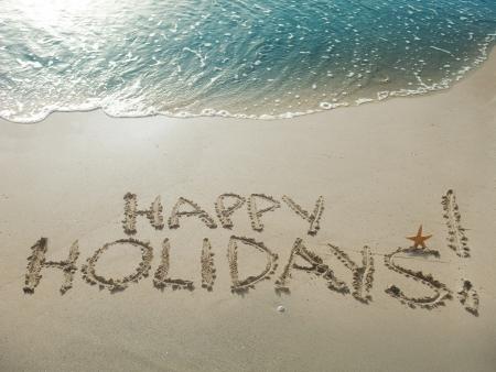 prázdniny: Happy Holidays! psaný v písku na pláži Reklamní fotografie