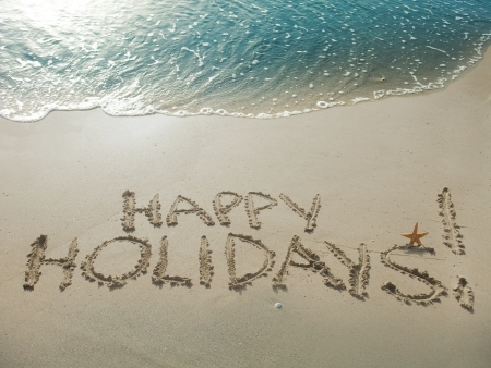 holiday: Happy Holidays! written in sand at the beach