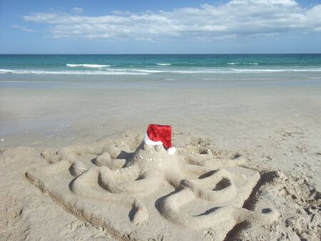 Sand made octopus at the beach in Santa hat Archivio Fotografico