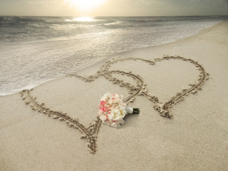 wedding beach: Two hearts hand drawn in sand at the beach  Bouquet of roses Stock Photo