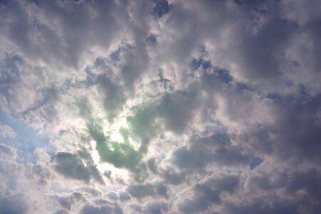 The sun hides behind dark blue clouds. Beautiful Cumulus clouds. Banco de Imagens