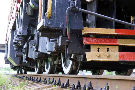 The wheels of the diesel locomotive on the rails. Railway transport.