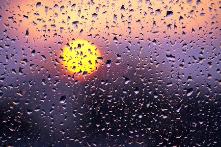 Raindrops on the glass and sunset. Weather forecast.