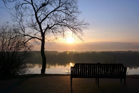 Morning dawn over the river with an empty bench in the Park. 免版税图像
