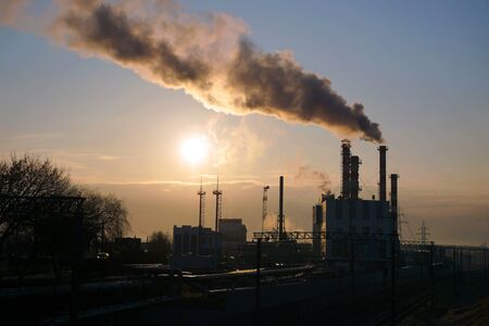 Morning dawn in a factory with industrial pipes and smoke. Pollution of the urban atmosphere. Environmental degradation.