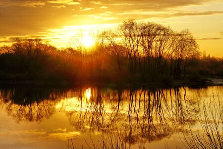 Magnificent morning spring dawn on the river. Sunrise behind the trees.