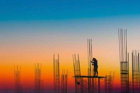 Silhouette construction industry of Engineer Business Concept with worker standing on safety stand from high ground and steel rod at Construction site on color grading technic background.