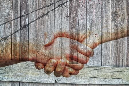 People shaking hands with fence on vintage wooden board wall background.A symbol sign of world war peace,harmony,tranquil,calm.Concept of Internationnal Peace Day.