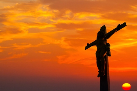 Silhouette of Jesus christ crucifix on cross over sunset and blue sky.Concept for Catholic religion, Christian worship, Christmas, Easter Day, Bible,Thanksgiving prayer and praise good Friday. Stock Photo