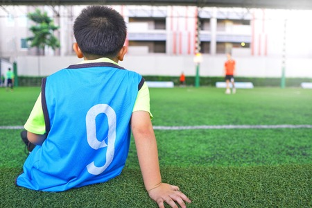 Asian young boy waiting on the football training.Children playing soccer on the beautiful turf sport field with sunlight in practicing day.Sports,Athlete,People,Health Care Concept.