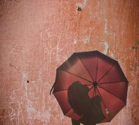 beautiful young woman with an umbrella against the sky photo