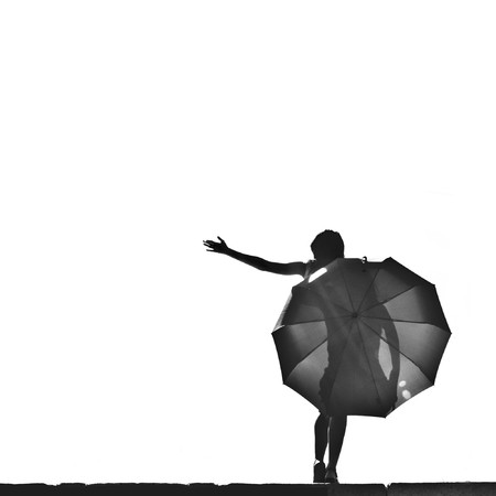 beautiful young woman with an umbrella against the sky Standard-Bild